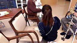 動物介在活動でセラピー犬を膝に乗せる参加者
